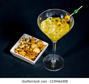 Close-up of cocktail martini with olives on table against isolated on black