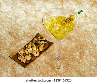 Close-up of cocktail martini with olives on table against with ration of nuts