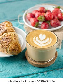 Closeup of coffee, croissant and fresh strawberries on a blue wooden background in grunge style.