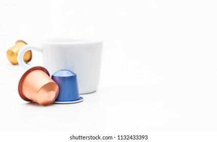 Closeup of coffee cup with espresso capsules