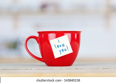 Closeup of coffee cup with I Love You tag on table in kitchen