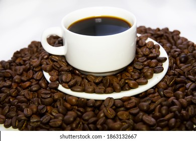 Close-up of coffee cup with roasted coffee beans surrounded by coffee beans