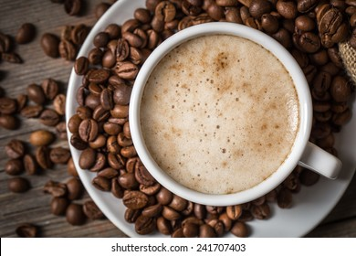Close-up of coffee cup with roasted coffee beans on wooden background. View from top