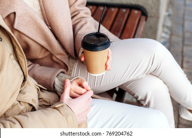 Closeup of coffee cups in hands of young couple having fun together on the street