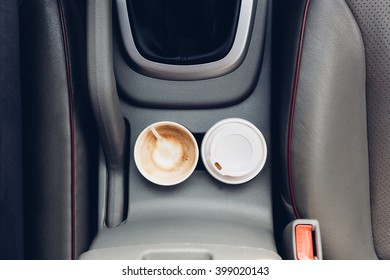 Closeup of coffee cups inside car holder between seats