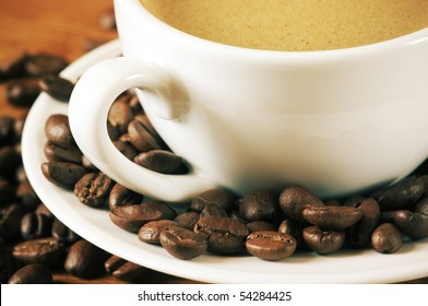Close-up of coffee with froth in white cup and coffee beans.