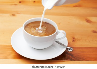 Closeup of coffee with milk being poured into the cup.  Shot on light wood background
