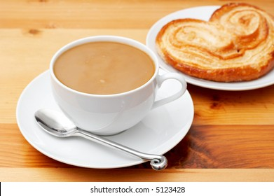Closeup of coffee with milk in white cup and a palmier pastry. Shot on light wood background