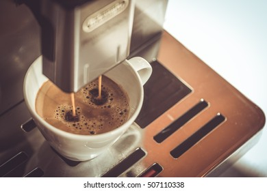 Close-up of coffee pouring from coffee machine into white cup at restaurant, bar or pub. Professional coffee brewing. Coffee break concept. Old fashioned sepia colors.