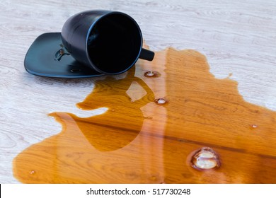 Closeup coffee spilled in black cup on wooden floor
