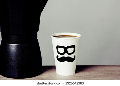 closeup of coffeemaker and a disposable cup with coffee, with a pair of glasses and a mustache drawn in it, depicting a man face, on a wooden table