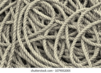 Closeup of a coil of old hemp rope. A high contrast monochrome edit.