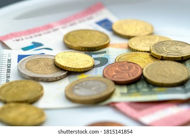 Close-up Of Coins And Currency Note On Plate. High Angle View. euro Money On White Plate. plate with coins and banknote. Toilet - Tip, church collection, rising costs, assets