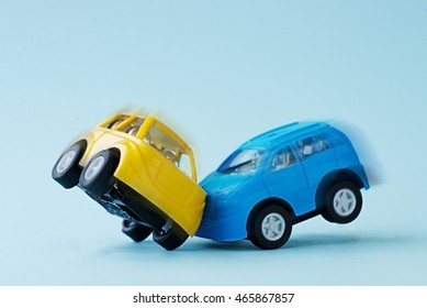 Close-up of a collision of two toy cars on a blue background