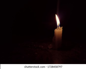 Closeup of Color and Grayscale Candle Light in a Dark Black Background.