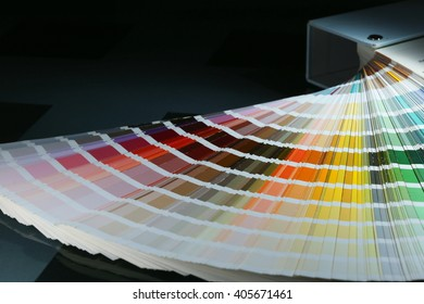close-up of color guide spread out like a fan on a dark background studio