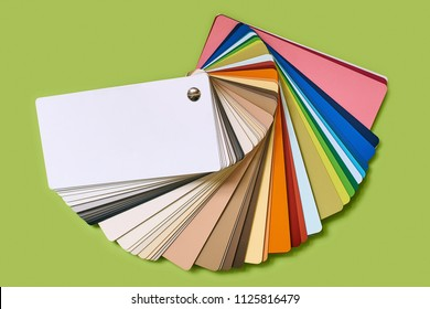 Close-up of color palette guide for furniture or catalog of wood-chip samples isolated on light letuce green background