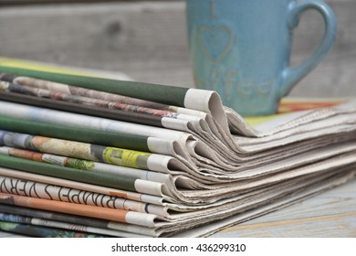 Closeup of color stacked newspapers on a wooden table background with a blue coffee mug