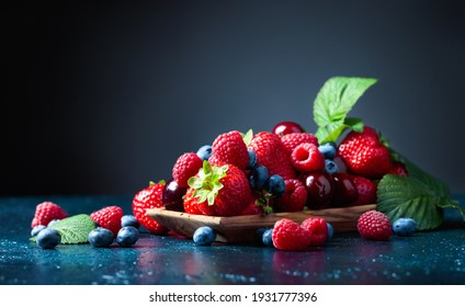 A close-up colorful assorted mix of strawberry, blueberry, raspberry, and sweet cherry in a studio on a dark blue background.