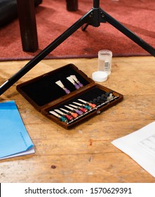 Closeup of colorful bassoon reeds on floor in rehearsal setting. Music stand, sheet music and small cup of water.