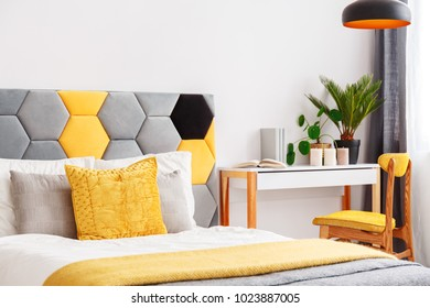 Close-up of colorful bed with hexagon bedhead in bright bedroom interior with yellow chair at wooden desk with plants and candles
