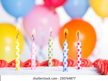 Closeup of colorful birthday candles on a cake with party balloons in background