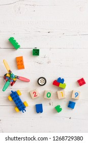 Closeup of colorful bricks and toys from plastic. Wooden cubes with the numbers of the year 2019 on a white wooden table. Early learning. Educational toys
