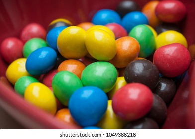 closeup of colorful chocolate candies in a red bowl in shaped heart