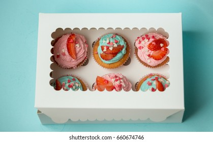 Closeup of  colorful cupcakes decorated with sprinkles and strawberries in closed paper box