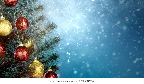 Closeup of colorful decorated chritmas tree with snowfall background