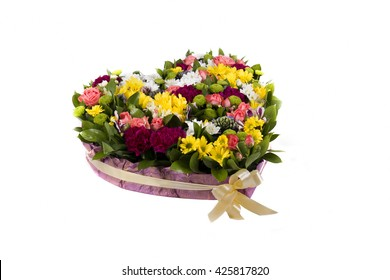 closeup of colorful flowers in basket in the form of heart isolated on white background. pink roses, camomiles and onther