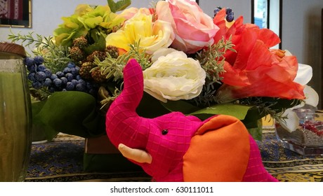 Pink elephant yellow flower images stock photos vectors closeup a colorful flowers vase with a pink elephant doll decors on dining table mightylinksfo