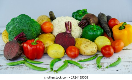closeup colorful fresh vegetable potato tomato lemon beetroot broccoli cabbage bell pepper peas carrot on white wooden table and white background