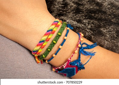 Closeup of a colorful friendship bracelet on a child's hand holding a cat