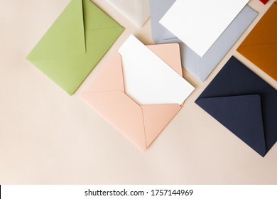 Close-up colorful mail envelopes on beige background flat lay with copy space, top view. Mailing concept isometric. White paper blank mockup for letters, greeting card, postcard, invitation