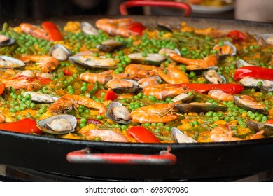 Closeup colorful paella with seafood cooked and served in large frying shallow pan, Spanish style and street food