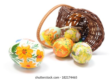 Closeup of colorful painted Easter eggs in overturned wicker basket, Easter decoration. Isolated on white background
