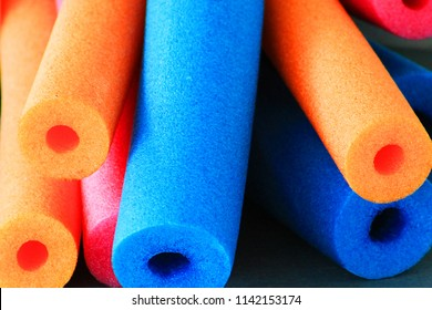 Close-up of colorful pool noodles, end view looking along noodles.