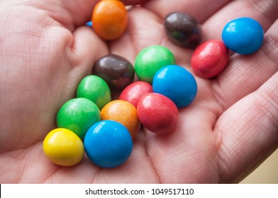 closeup of colorful round chocolate candies in hand