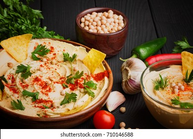 A close-up of a colorful snack composition on a black wooden background. Delicious hummus in glass bowl and on a wooden plate.