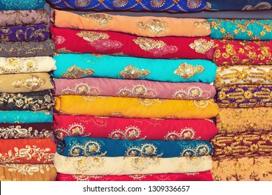 Closeup of colorful textiles in vivid colors, golden ornaments on all of the fabrics. Global Village, Dubai