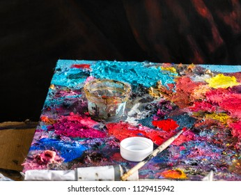Closeup colorful and texture of oil color on palette of the artist with paintbrush with linseed oil in cup and oil color tube