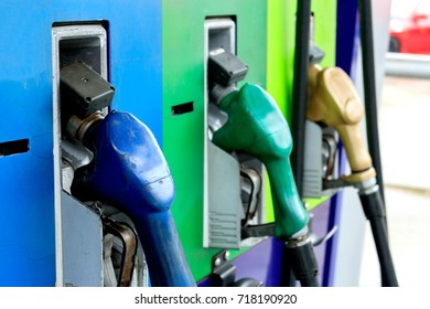 closeup of colourful fuel pumps at a gas station with soft-focus and over light in the background
