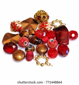 Close-up of a colourful mix of round, oval beads that sparkle in red and gold. Decorative ornaments for hobbies including jewellery making and crafts. Used to make necklaces and bracelets.