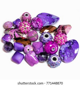 Close-up of a colourful mix of round, oval and fancy shaped beads in vibrant purple and pink. Sparkling, decorative ornaments for hobbies including jewellery making and crafts. Used to make necklaces