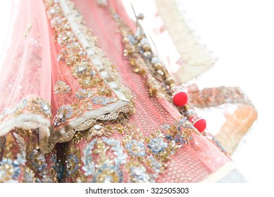 Closeup colourful traditional indian bride dress on white background. Selective focus.