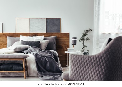 Close-up of comfy, gray armchair facing white bed with gray bedsheets and wooden bedhead in cozy bedroom interior