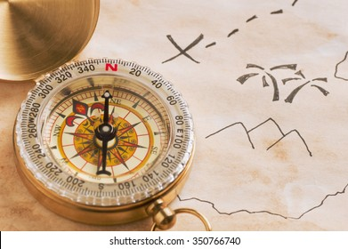 Closeup of compass lying over stained yellowed paper sheet with part of schematic hand drawn treasure map. Focused on compass. Concept of treasure hunt or adventure travel.