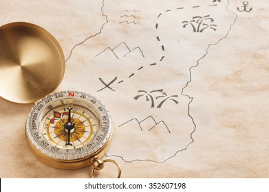 Closeup of compass over stained yellowed paper sheet with part of schematic hand drawn treasure map