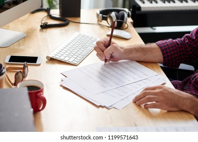 Close-up of composer sitting at the table with sheets of paper and composing music